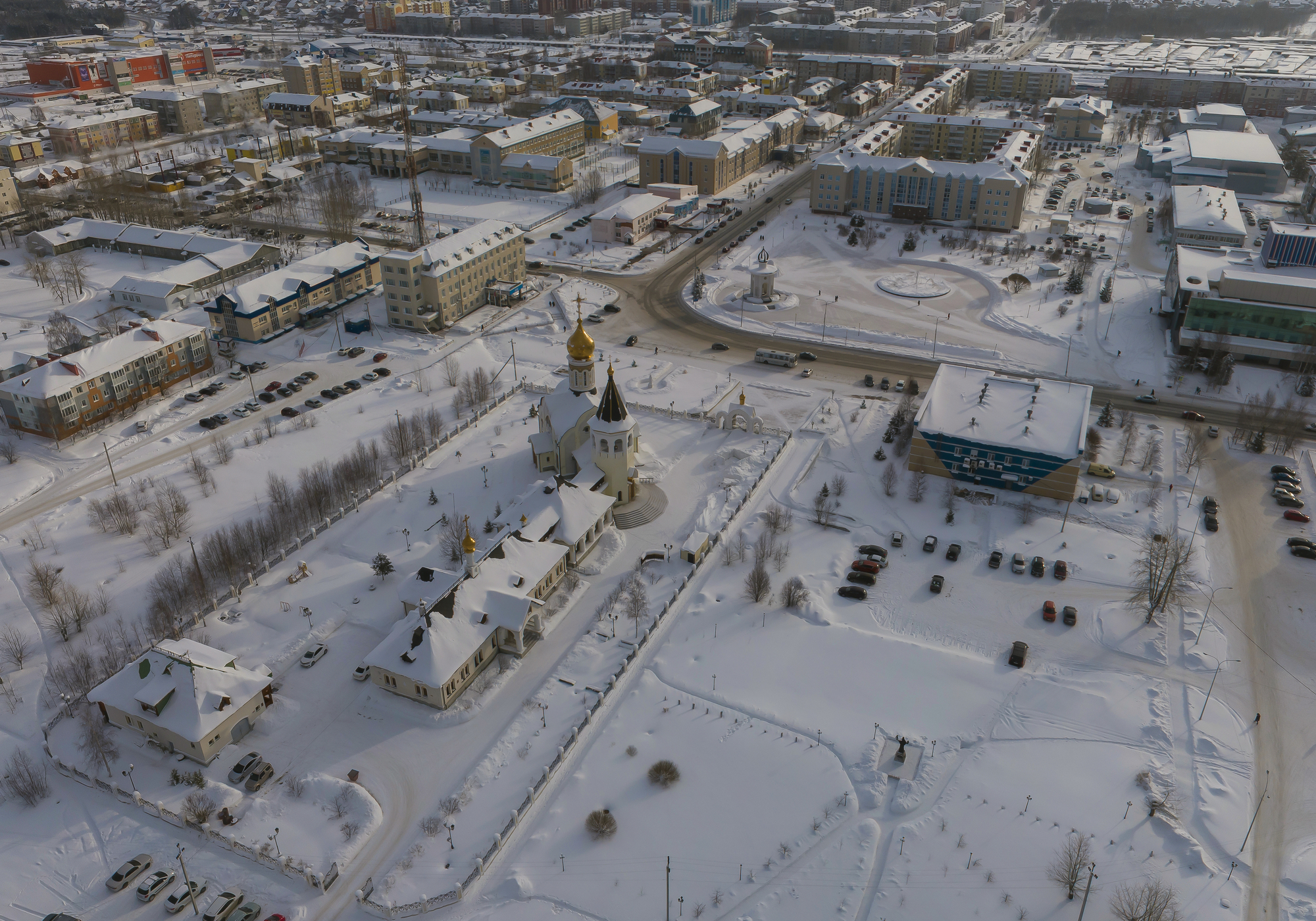 Church and city administration building  in Yugorsk city. Aerial. Winter, snow, cloudy. Khanty Mansiysk Autonomous Okrug (HMAO), Russia.